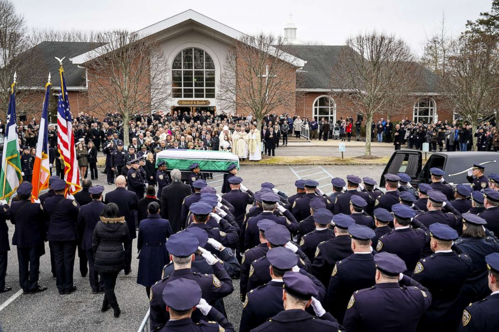 PHOTO: Police officers salute as the remains of fallen NYPD Detective Brian Simonsen are carried toward a Hearse following his funeral service at the Church of St. Rosalie, Feb. 20, 2019, in Hampton Bays, N.Y.