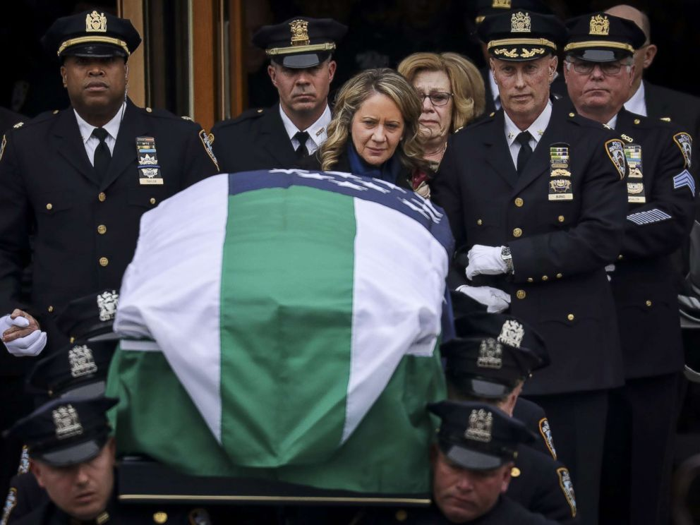 PHOTO: Leanne Simonsen, wife of fallen NYPD Detective Brian Simonsen, is escorted by officers as her late husbands remains are carried out of the church following his funeral service at the Church of St. Rosalie, Feb. 20, 2019 in Hampton Bays, N.Y.