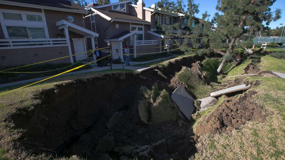 A sinkhole is seen in a condominium complex, Jan. 24, 2019, in La Habra, Calif. The hole is estimated to be about 80 feet  long and 20 feet wide.