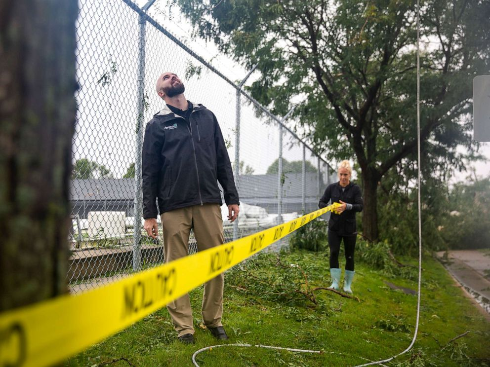 PHOTO: Whitnee Fester puts up caution tape outside of the Avera dome after a devastating tornado hit in Sioux Falls, S.D., Sept. 11, 2019.