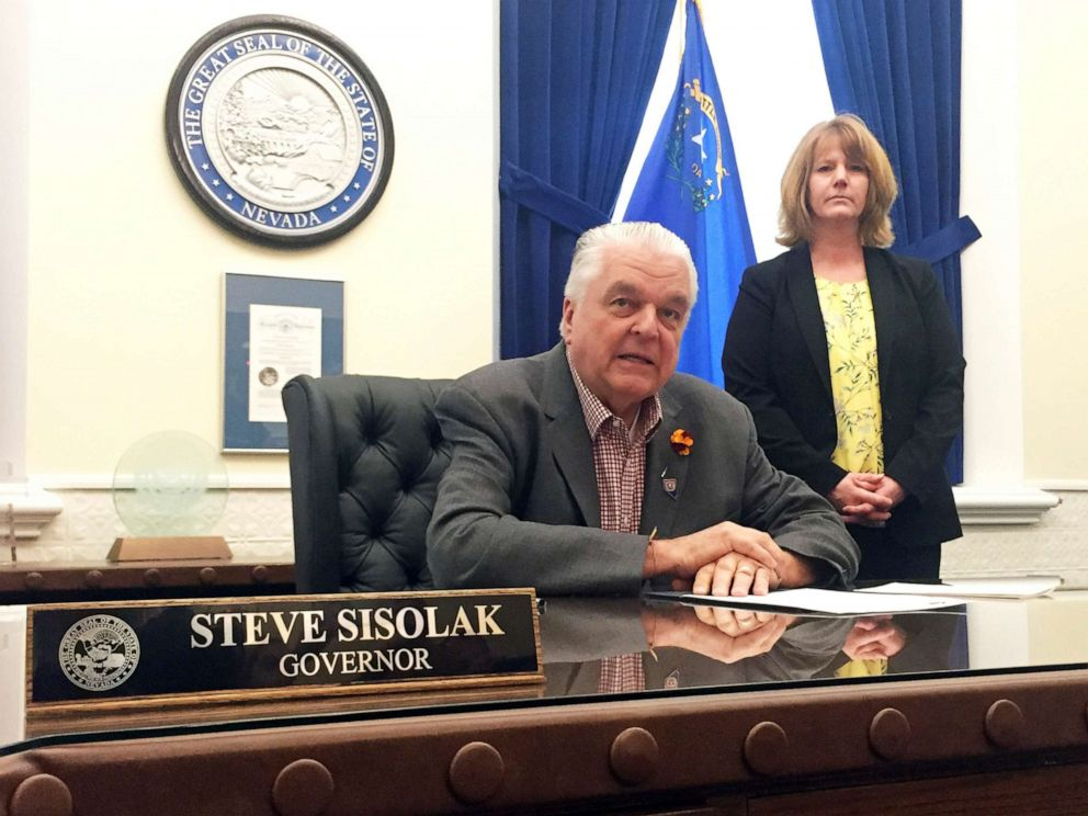 PHOTO: Nevada Gov. Steve Sisolak sits at his desk at the Capitol in Carson City before signing a bill that opens the books on applications for licenses to sell recreational marijuana on May 10, 2019.