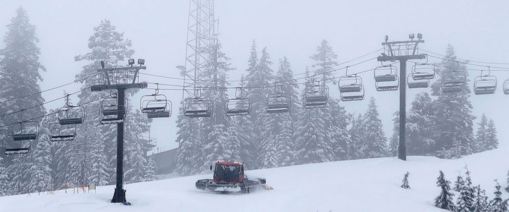 PHOTO: A snow grooming machine works along a chairlift at The Summit at Snoqualmie Ski Area as fresh snow falls, Feb. 14, 2018, in Snoqualmie Pass, Wash.