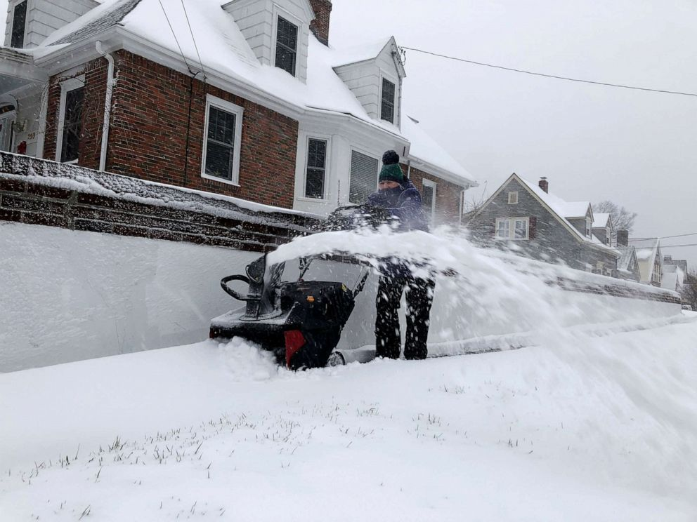 PHOTO: Doreen Goy, of Warwick, R.I., uses a snowblower to clear a sidewalk after a second round of snow struck the area, Dec. 3, 2020.