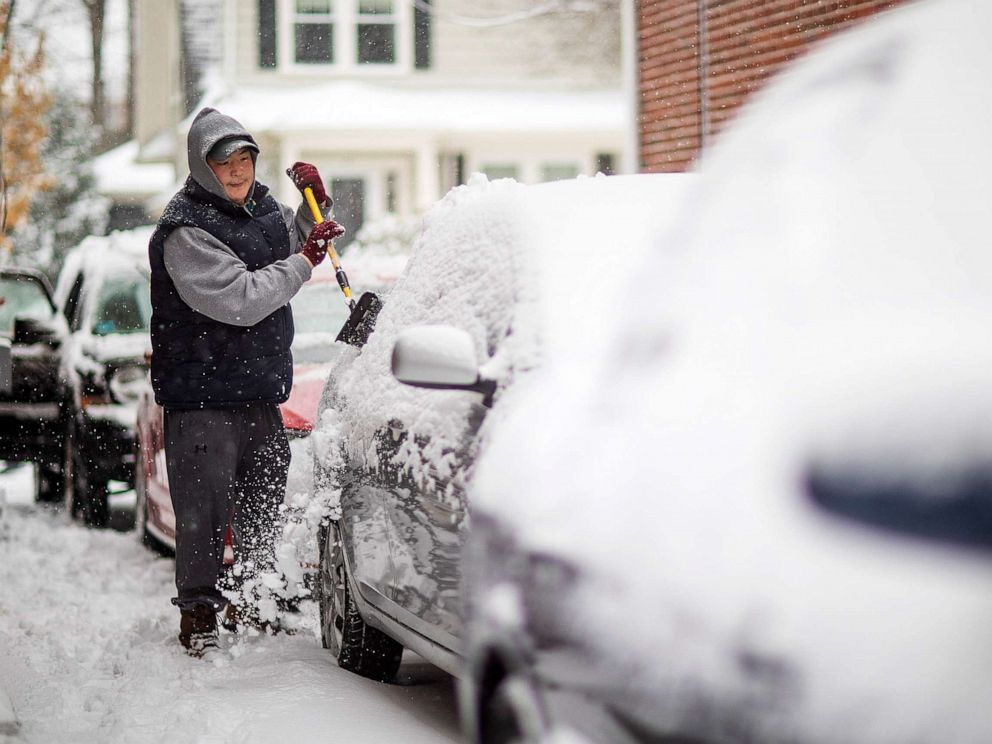PHOTO: Benjamin Shoquette clears snow off his car outside his home, Dec. 3, 2019, in Providence, R.I.