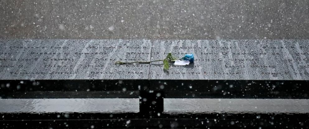 PHOTO: A memorial flower is left by a name at the 9/11 Memorial during a wet snowfall, Thursday Nov. 15, 2018, in New York.