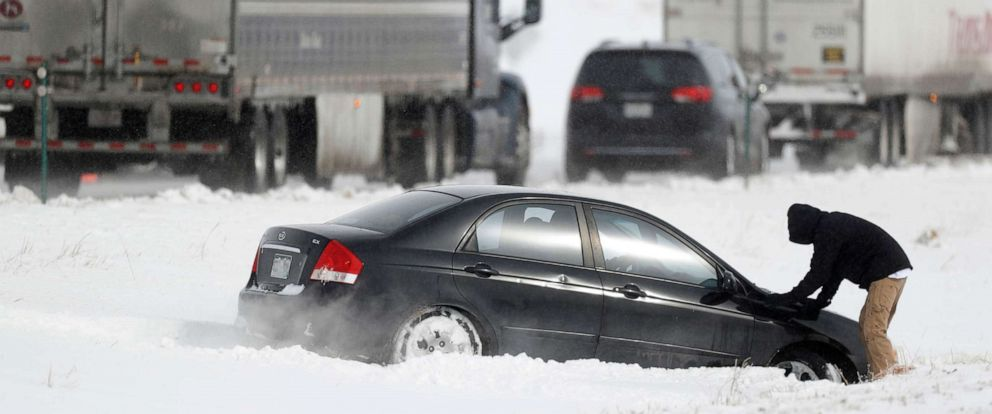 PHOTO: A file photo of a motorist as he struggles to free his sedan after sliding off Interstate 70, which was later closed by officials, in Aurora, Colo., Oct. 29, 2019.