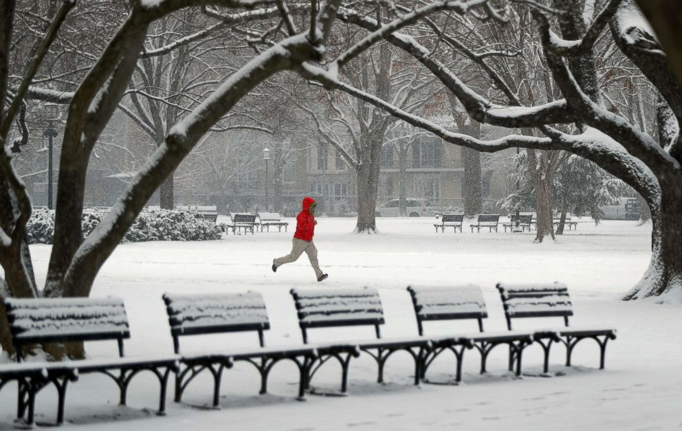 A man runs through Lafayette Park in front of the White House during a snowstorm in Washington, D.C., Feb. 20, 2019.