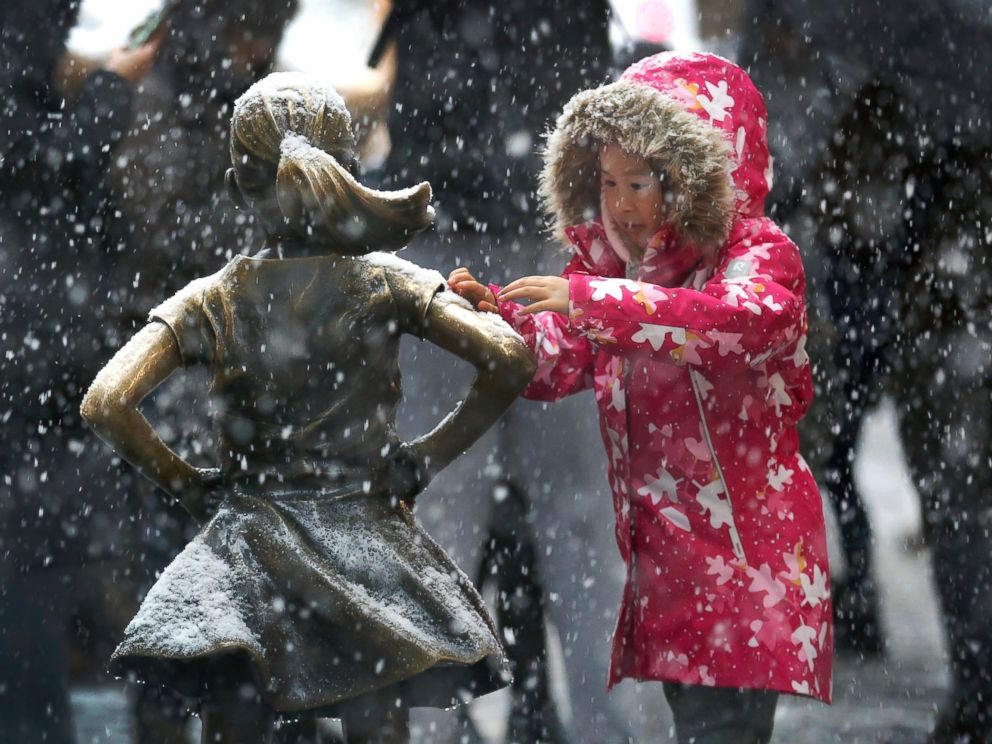 PHOTO: A young girl brushes off snow on the Fearless Girl statue in lower Manhattan on Thursday, Nov. 15, 2018, in New York. One of the first big storms of the season moved across the eastern half of the country on Thursday.