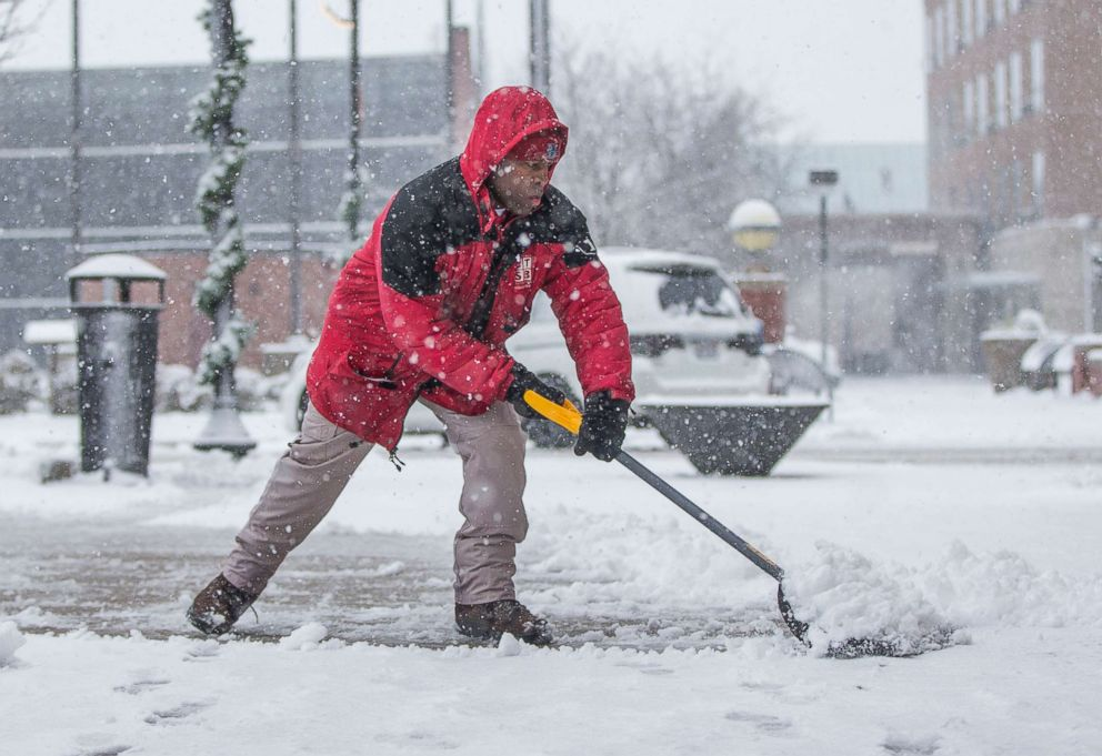 Terrance Pates, of Downtown South Bend, clears a sidewalk along Michigan Avenue on  Nov. 26, 2018, in South Bend, Ind.