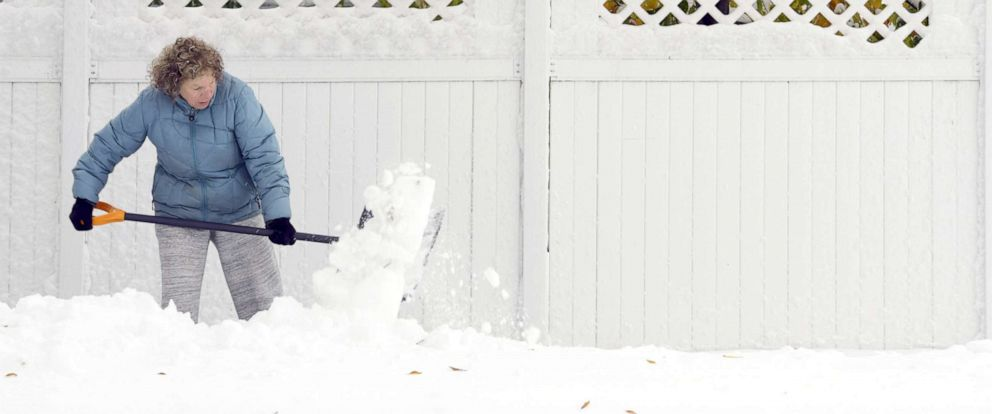 PHOTO: Anne Haugarth shovels the heavy, wet snow from a sidewalk in front of her home, Oct. 11, 2019, in Bismarck, N.D.