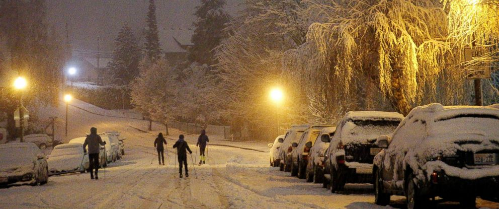 PHOTO: Cross-country skiers travel on a street in Tacoma, Wash., the night of Friday, Feb. 8, 2019, during a storm that dropped inches of snow throughout the region and left trees and cars coated in snow and ice.