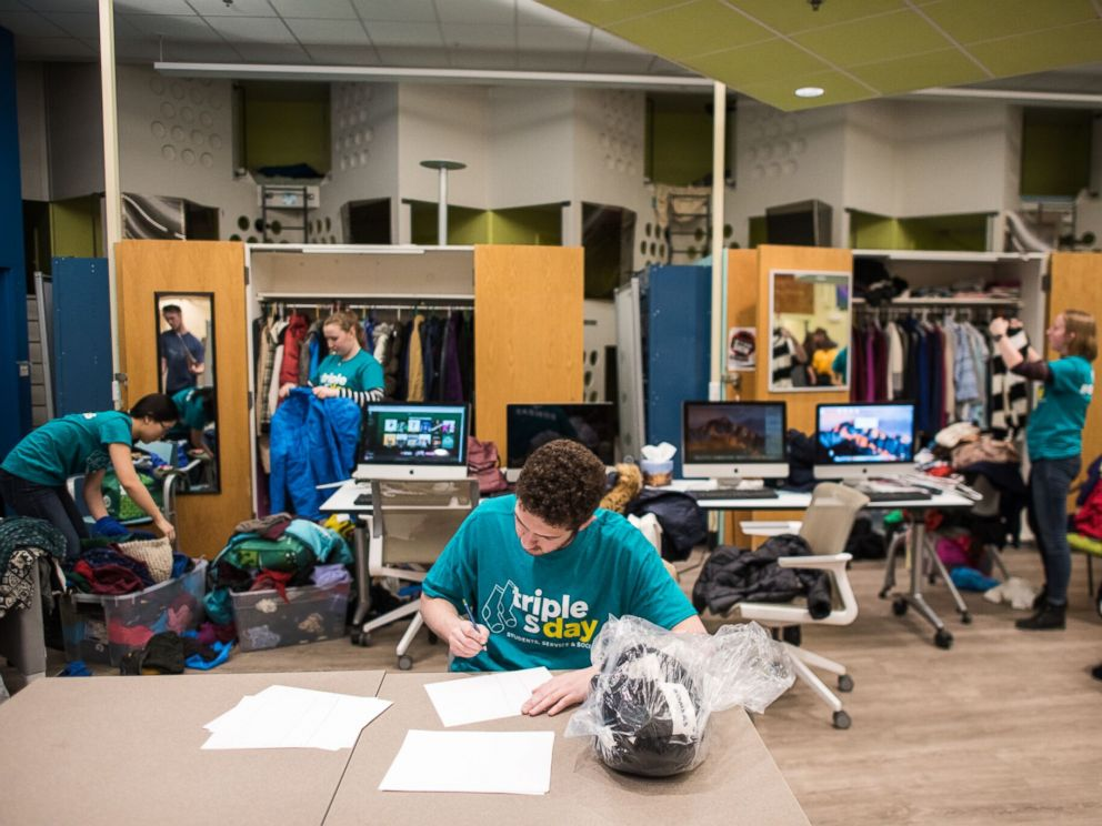 PHOTO: Boston-area college students help organize donated clothing items at a Boston homeless shelter.
