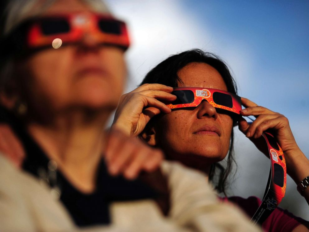 PHOTO: Ina Schakaraschwili holds her glasses in place during a solar eclipse at the University of Denvers Chamberlain Observatory in this May 20, 2012 file photo