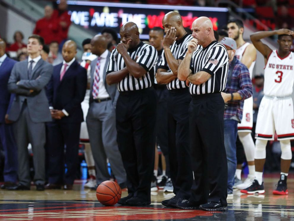 PHOTO: Game 0fficials including from left, Les Jones, Bert Smith and Tim Comer, watch as South Carolina States Tyvoris Solomon is attended to after he was injured during an NCAA college basketball at PNC Arena in Raleigh, N.C., Dec. 2, 2017.