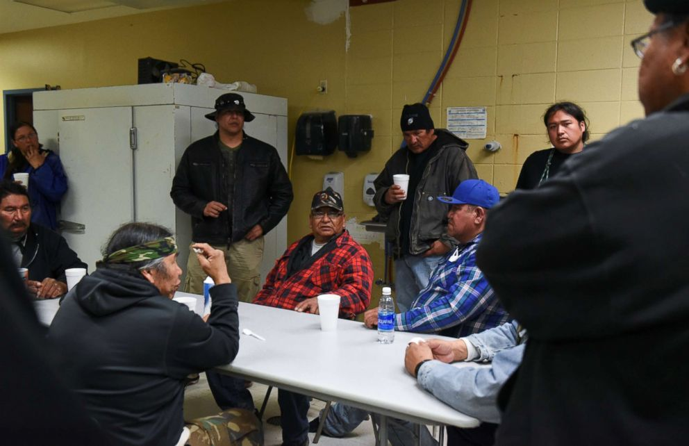 PHOTO: Ivan Lookinghorse (C) and other Fort Laramie treaty riders meet in the kitchen of the Rockyford School gymnasium on the Pine Ridge Reservation in Rockyford, South Dakota, April 20, 2018.