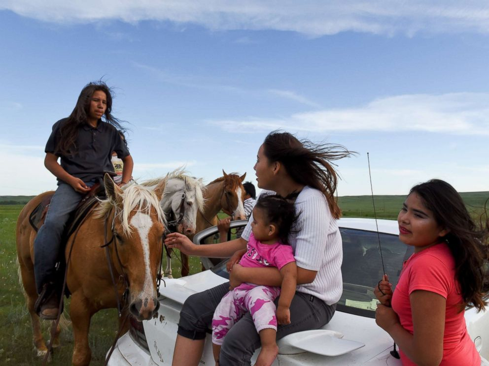 PHOTO: Angel Rose Lookinghorse, sitting with her younger cousins, Linda Lookinghorse and Maryann Lara, as she speaks to her brother, Jayden Lookinghorse, on horseback, at the Cheyenne River Reservation in Green Grass, South Dakota, May 31, 2018.