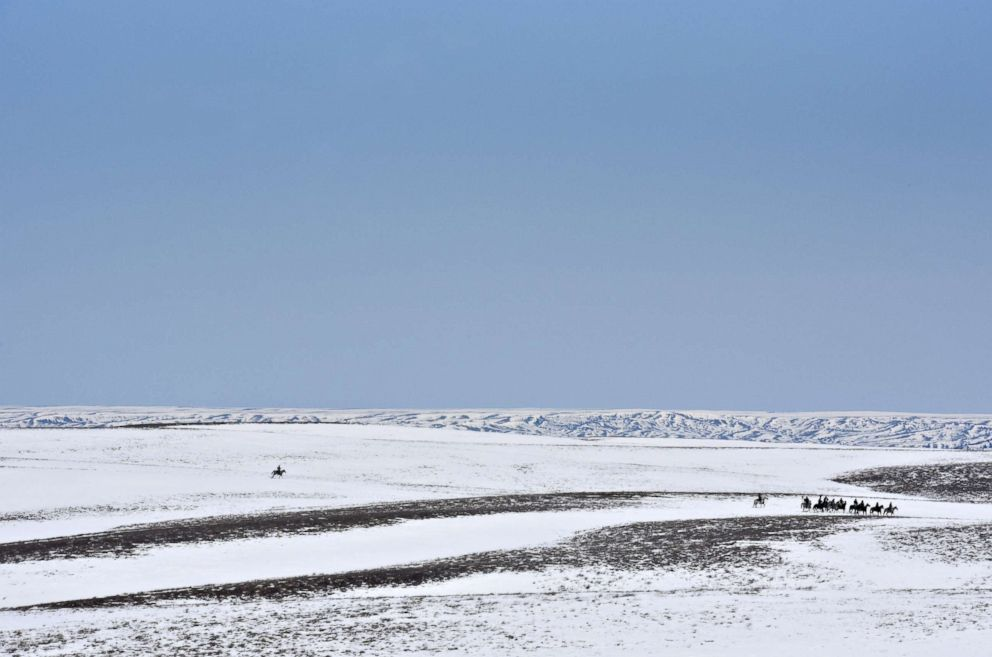 PHOTO: A group of Lakota riders make their way across a snowy field on the second day of their treaty ride on the Cheyenne River Reservation near Howes, South Dakota, April 15, 2018.