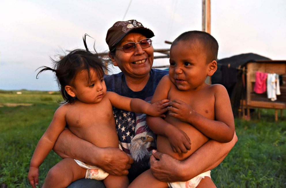 PHOTO: Beatrice Lookinghorse holds two of her grandchildren, Linda Lookinghorse and Cody James Lookinghorse, in the backyard of her home on the Cheyenne River Reservation in Green Grass, South Dakota, May 28, 2018.