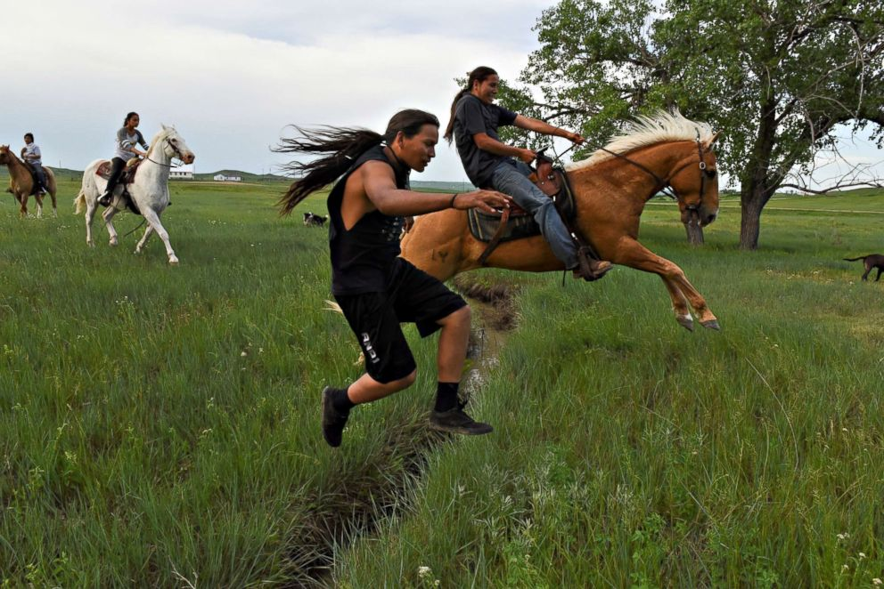 PHOTO: Mahto In The Woods jumps a small creek on foot while his cousin Jayden Lookinghorse jumps over on his horse on the Cheyenne River Reservation in Green Grass, South Dakota, May 31, 2018.