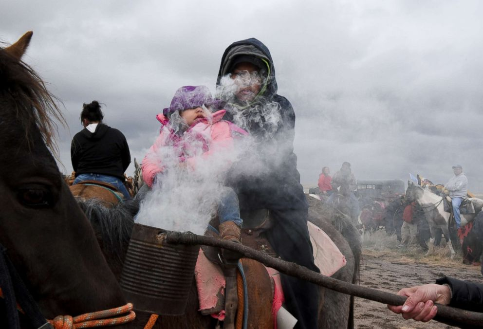 PHOTO:Fort Laramie treaty rider, Austin Warrior, 11, and his sister Delores Warrior, 19 months, both from Pine Ridge Reservation are covered with burning sage smoke in Harrison, Nebraska, April 24, 2018.