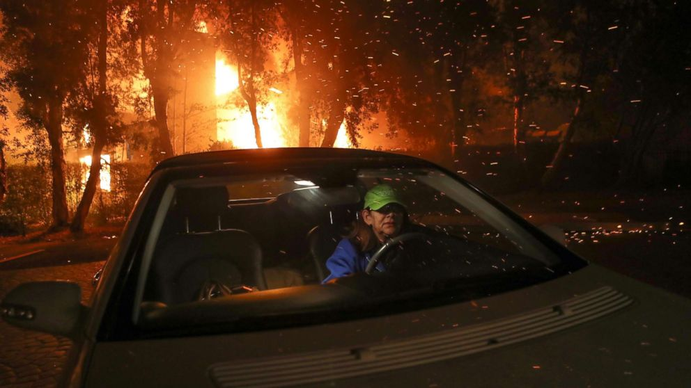 Tina Weeks jumps into her car to evacuate after her neighbors house became fully engulfed by the Woolsey Fire in Oak Park, Ca., in the early morning of Nov. 9, 2018.