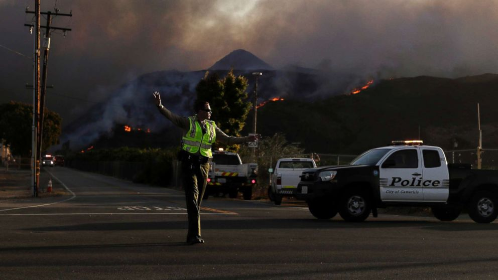 A police officer mans a checkpoint in front of an advancing wildfire Thursday, Nov. 8, 2018, near Newbury Park, Calif.