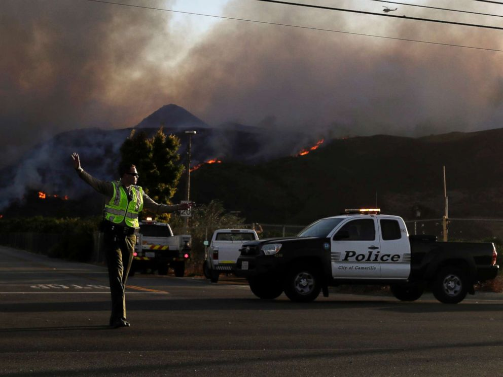 PHOTO: A police officer mans a checkpoint in front of an advancing wildfire Thursday, Nov. 8, 2018, near Newbury Park, Calif.