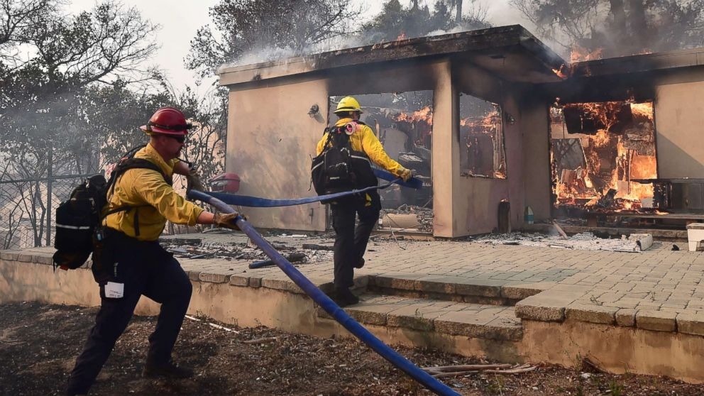 Firefighters knock down flames in the Point Dume neighborhood of Malibu, Calif., on Nov. 10, 2018, after the Woolsey Fire tore through the neighborhood overnight.