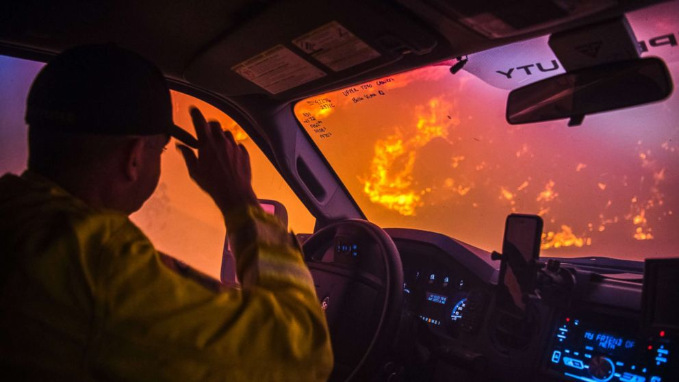Cal Fire battalion chief and strike team leader Gino DeGraffenreid drives past a flaming hillside while checking on homes Monday night in Toro Canyon, Calif. at the Thomas Fire on Dec. 11, 2017.