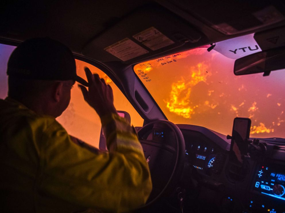 PHOTO: Cal Fire battalion chief and strike team leader Gino DeGraffenreid drives past a flaming hillside while checking on homes Monday night in Toro Canyon, Calif. at the Thomas Fire on Dec. 11, 2017.