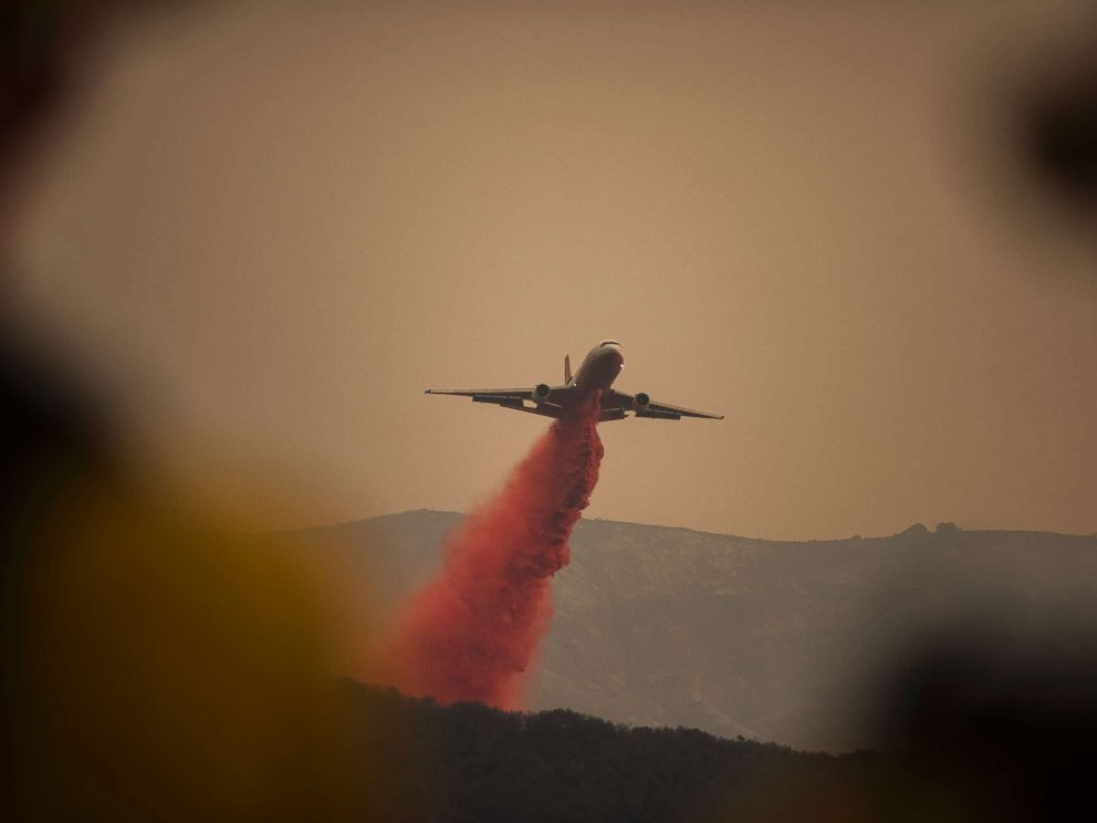 PHOTO: A DC-10 jet, or VLAT (Very Larger Air Tanker) drops fire retardant in Toro Canyon, Calif. on Monday afternoon, Dec. 11, 2017, before anticipated winds caused the fire to burn downhill.