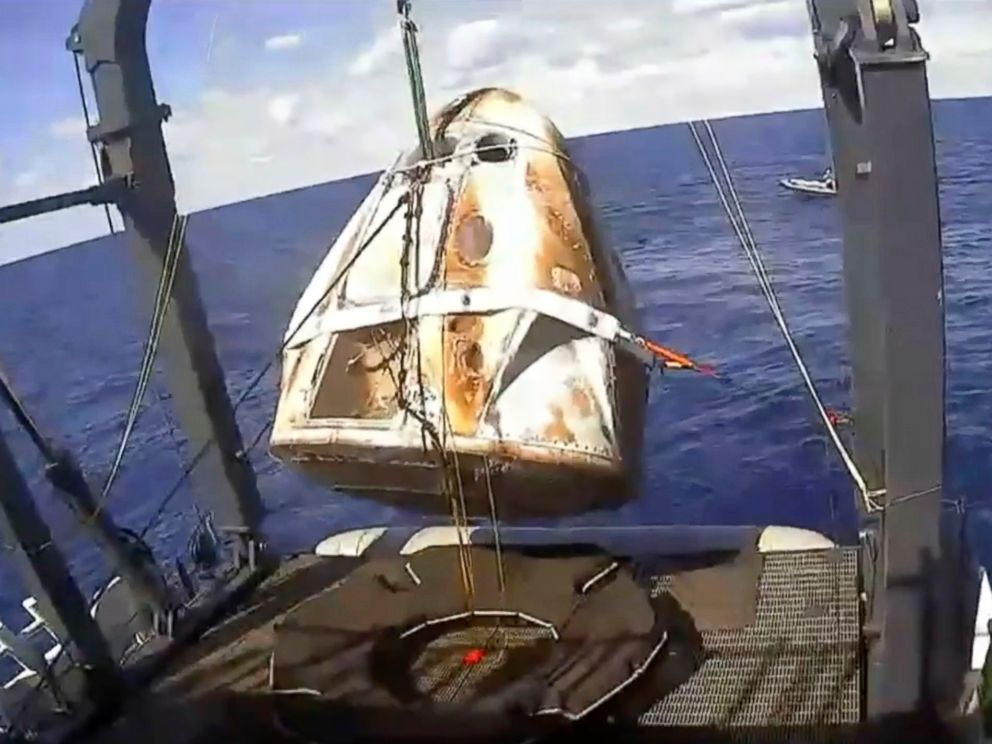 PHOTO: In this image from video made available by NASA, the SpaceX Crew Dragon capsule is hoisted onto a ship in the Atlantic Ocean off the Florida coast after it returned from a mission to the International Space Station, March 8, 2019.