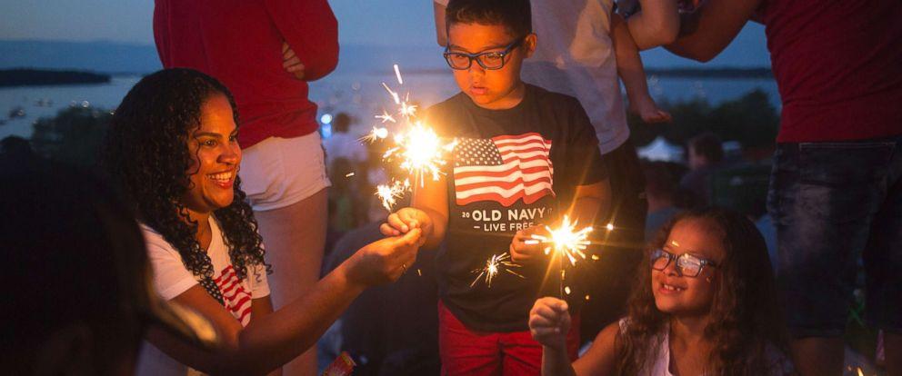 PHOTO: Debra Orellana, Erik Orellana, 6, and Vanessa Orellana, of Portland, light sparklers as they wait to watch the fireworks at the Fourth of July celebration on the Eastern Promenade.