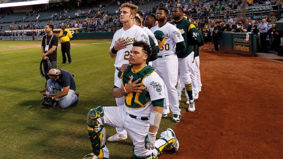 Bruce Maxwell #13 of the Oakland Athletics kneels during the national anthem in front of teammate Mark Canha #20 before the game against the Seattle Mariners at the Oakland Coliseum, Sept. 25, 2017 in Oakland, California.