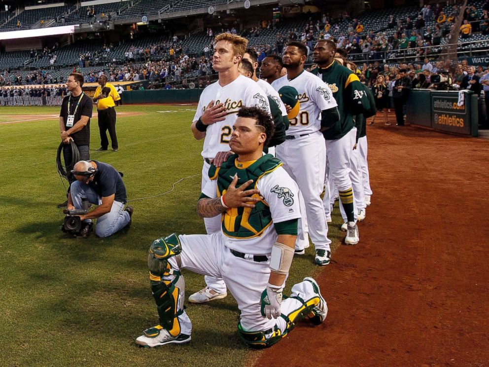 PHOTO: Bruce Maxwell #13 of the Oakland Athletics kneels during the national anthem in front of teammate Mark Canha #20 before the game against the Seattle Mariners at the Oakland Coliseum, Sept. 25, 2017 in Oakland, California.