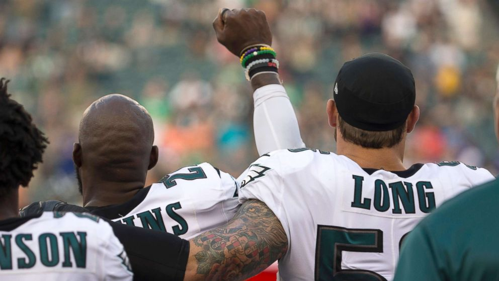 Malcolm Jenkins #27 of the Philadelphia Eagles holds his fist in the air during the national anthem while Chris Long #56 of the Philadelphia Eagles puts his arm around him prior to the preseason game against the Buffalo Bills at Lincoln Financial Field, Aug. 17, 2017 in Philadelphia.