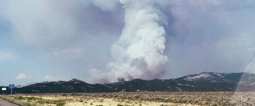 Smoke looms near La Veta Pass in Costillo County in southern Colorado, from one of several wildfires burning in Colorado and Utah, Thursday, June 28, 2018. Authorities say some structures have been burned by what is called the Spring Fire.