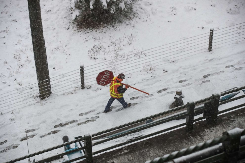 PHOTO: A construction worker carries a stop sign in the snow near the Brooklyn Bridge Park and I-278, April 2, 2018 in the Brooklyn borough of New York.