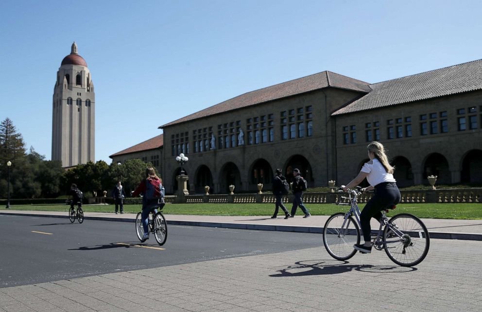 PHOTO: Cyclists ride by Hoover Tower on the Stanford University campus, March 12, 2019, in Stanford, Calif.
