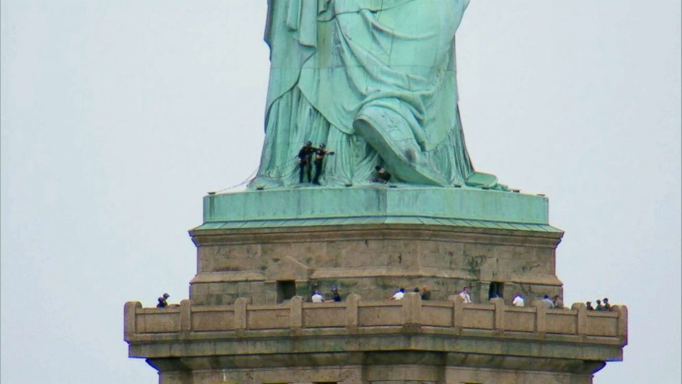 PHOTO: Police approach a woman who climbed the base of the Statue of Liberty in New York City on July 05, 2018.