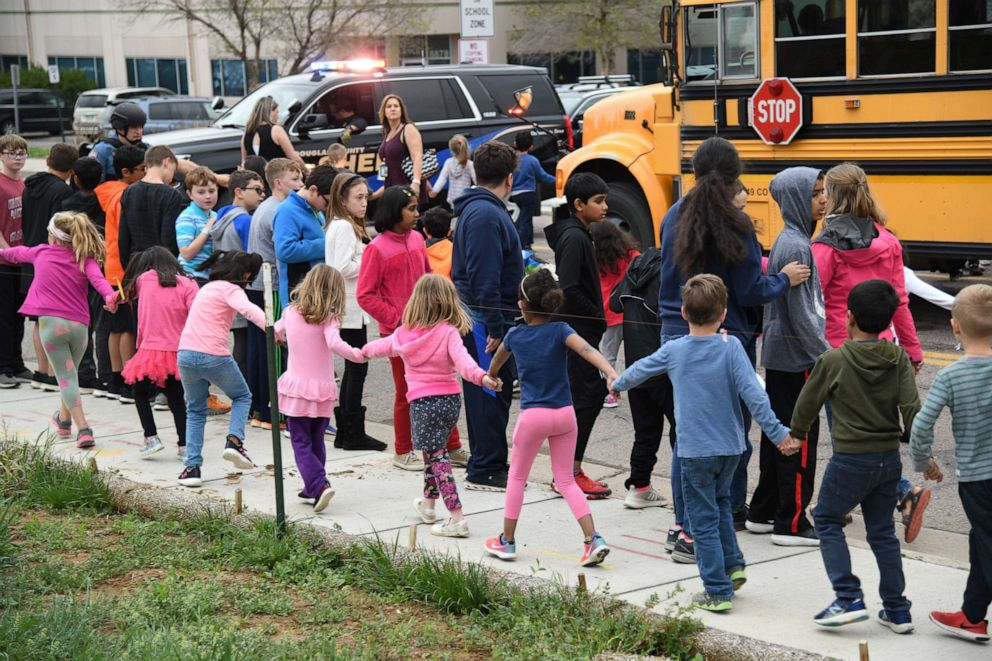 PHOTO: Students are escorted to a school bus in front of STEM School Highlands Ranch after a shooting, May 7, 2019, in Highlands Ranch, Colo.