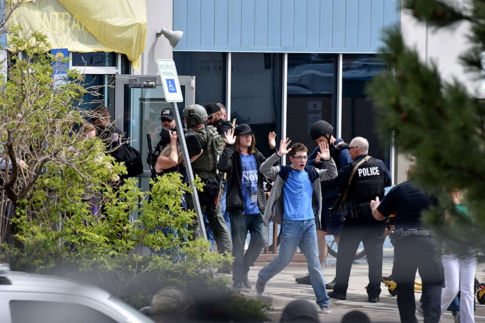 PHOTO: Students and teachers raise their arms as the exit the scene of a shooting in which at least seven students were injured at the STEM School Highlands Ranch, May 7, 2019, in Highlands Ranch, Colorado.