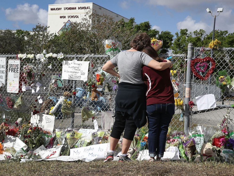 PHOTO: Joellen Berman, Guidance Data Specialist, and Margarita Lasalle, the budget keeper, look on at the memorial in front of Marjory Stoneman Douglas High School as teachers and staff are allowed to return to the school, Feb. 23, 2018, in Parkland, Fla.
