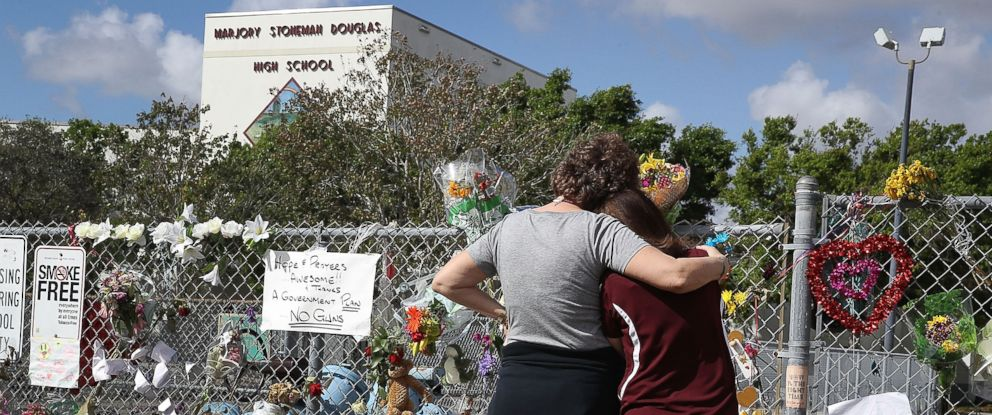 PHOTO: Two women look on at the memorial in front of Marjory Stoneman Douglas High School as teachers and staff are allowed to return to the school for the first time since the mass shooting on campus, Feb. 23, 2018, in Parkland, Fla.