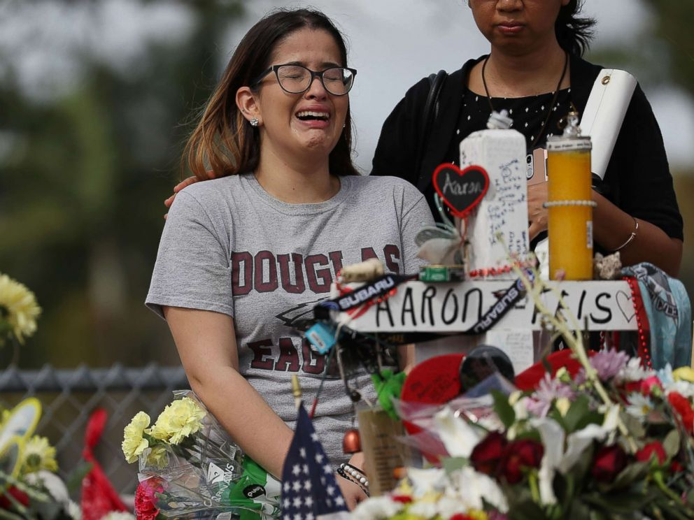 PHOTO: Ariana Gonzalez is over come with emotion as she visits a cross setup for her friend, football coach Aaron Feis, at the memorial in front of Marjory Stoneman Douglas High School, Feb. 23, 2018 in Parkland, Florida.