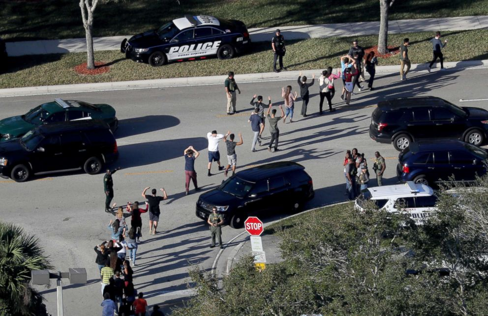 PHOTO: Students hold their hands up as they are evacuated by police from Marjory Stoneman Douglas High School in Parkland, Fla., after a shooter opened fire on the campus on Feb. 14, 2018.
