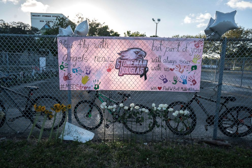 PHOTO: Signs and flowers are displayed by the fence surrounding Marjory Stoneman Douglas High School in Parkland, Fla., Feb. 25, 2018.