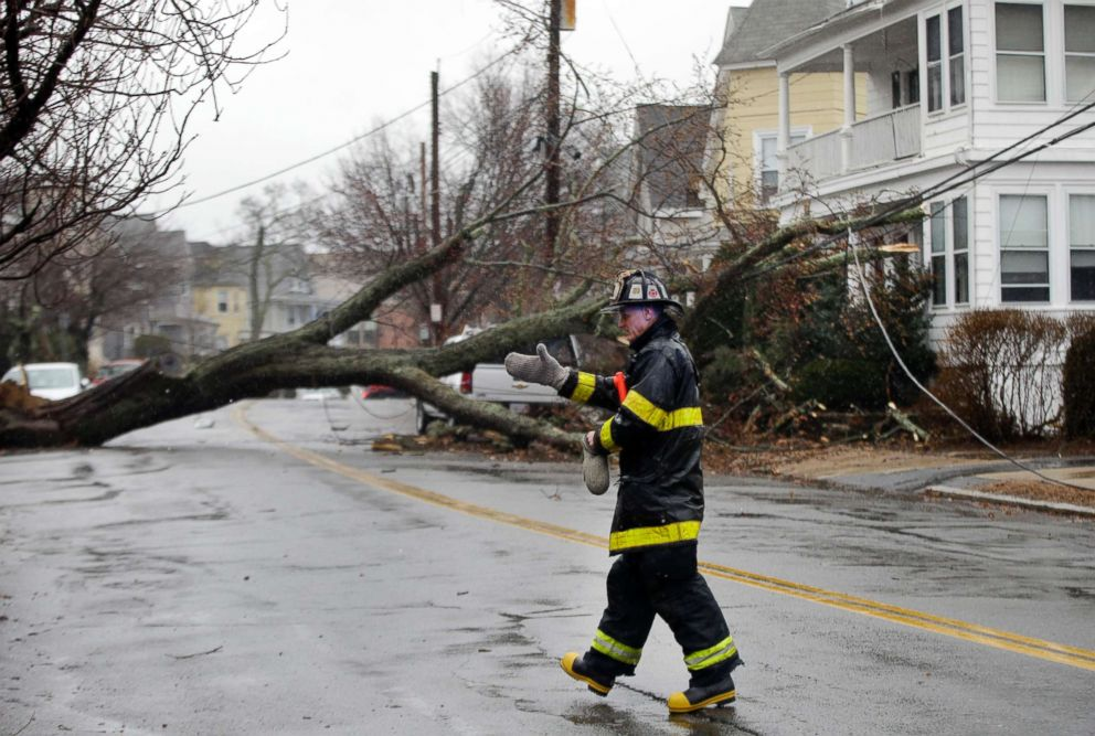 PHOTO: A firefighter instructs a pedestrian to keep back from an uprooted tree blocking a residential street and downed power line, March 2, 2018, in Swampscott, Mass.