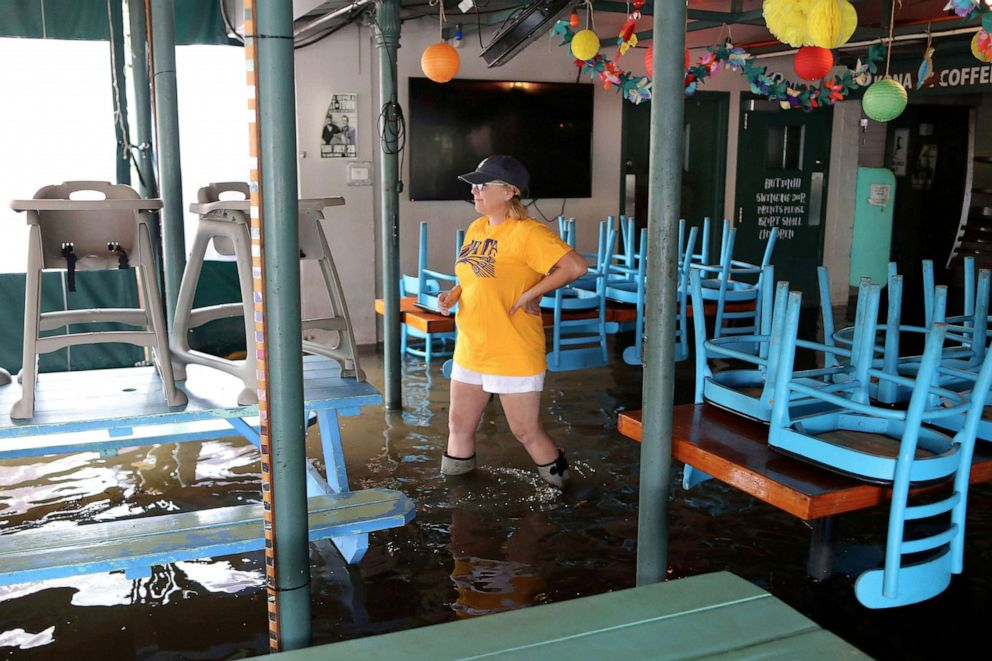 PHOTO:A woman walks through her flooded business during Hurricane Barry in Mandeville, Louisiana, July 13, 2019.