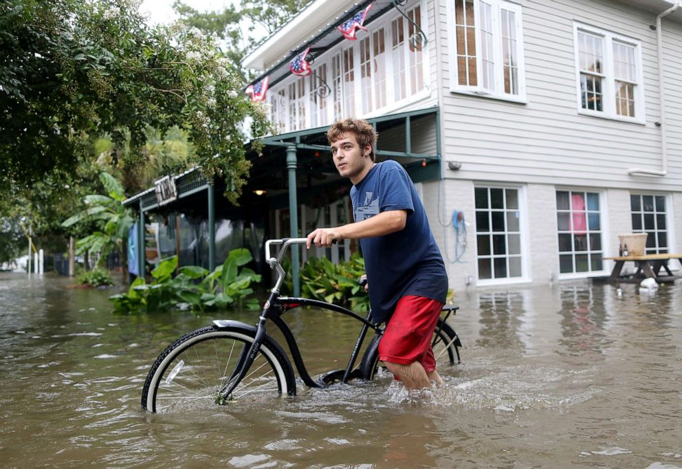 PHOTO: A man pushes his bike through a flooded street after Hurricane Barry in Mandeville, La., July 13, 2019.